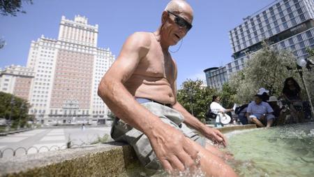 Un hombre se resfresca en la fuente de Plaza de España