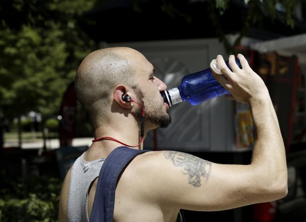 Un hombre bebe en el parque del Retiro de Madrid para hacer frente a las altas temperaturas