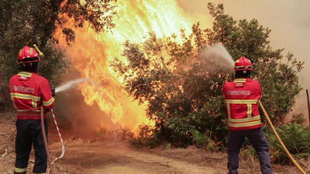 Dos bomberos portugueses combaten el fuego en Sandinha (Portugal) el pasado 20 de junio