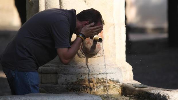 Un hombre se refresca en una fuente de Córdoba durante la ola de calor de junio