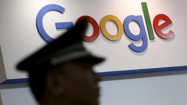 Fotografía de archivo de un guardia de seguridad que camina junto al logo de Google en Shanghai, China