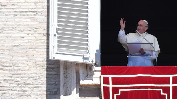 El Papa Francisco saluda a la multitud desde la ventana del palacio apostólico que domina la plaza de San Pedro durante la oración del Angelus dominical