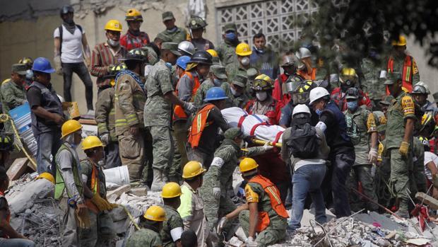 Brigadistas y voluntarios trabajan entre los escombros de los edificios colapsados durante un sismo de magnitud 7,1