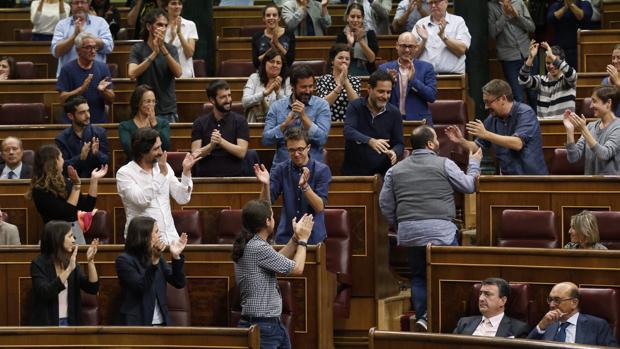 Los diputados de Podemos, que se opusieron a la moción, aplauden la intervención de su portavoz