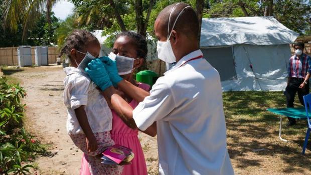 Un médico coloca una mascarilla a una niña en un centro de Toamasina (Madagascar)