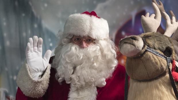 Un hombre disfrazado de Papá Noel saluda a los visitantes