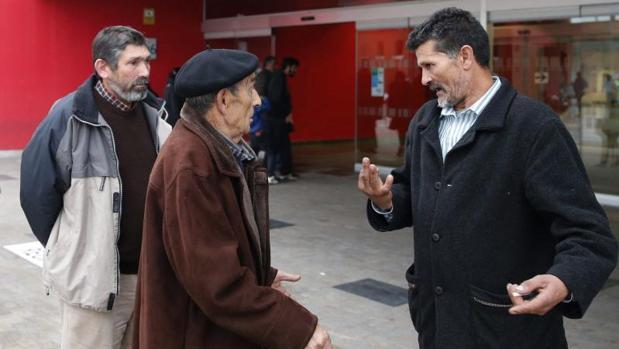 José Carlos Giménez (d), el padre del interno de la prisión de Asturias al que los médicos dieron por muerto y que recobró ayer el conocimiento después de trasladarle al Instituto Anatómico Forense para practicarle la autopsia, conversa con familiares, esta tarde en la entrada del Hospital Universitario Central de Asturias (HUCA)