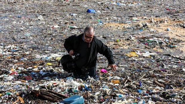 Un periodista libanés camina entre montañas de basura