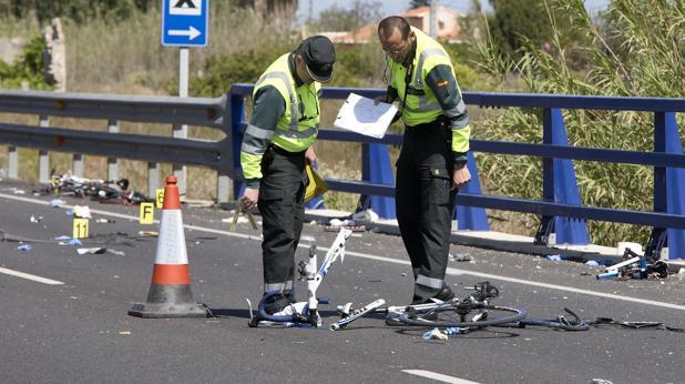 La Guardia Civil observa los restos de una bicicleta, después de un atropello masivo