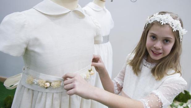 aa17dcce2f Sociedad Una niña se prueba el vestido de su Comunión en la tienda de  Cáritas en la