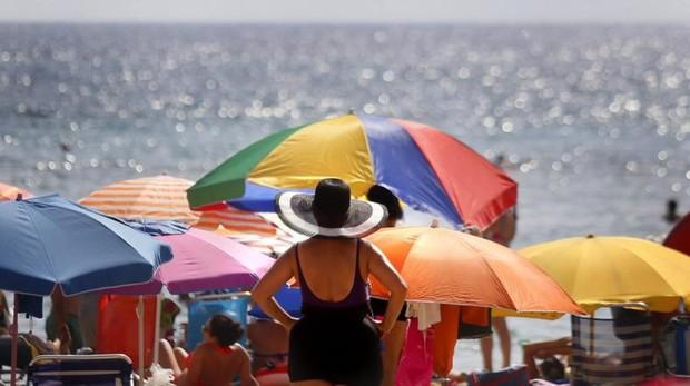 Turistas disfrutan del sol y el agua en la playa de Levante de Benidorm
