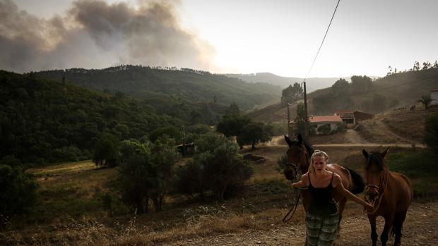 Una mujer tira de dos caballos mientras una columna de humo de alza detrás suyo cerca de la Sierra de Monchique, donde 30 bomberos tuvieron que ser atendidos por los efectos del calor o por inhalaciones de humo.