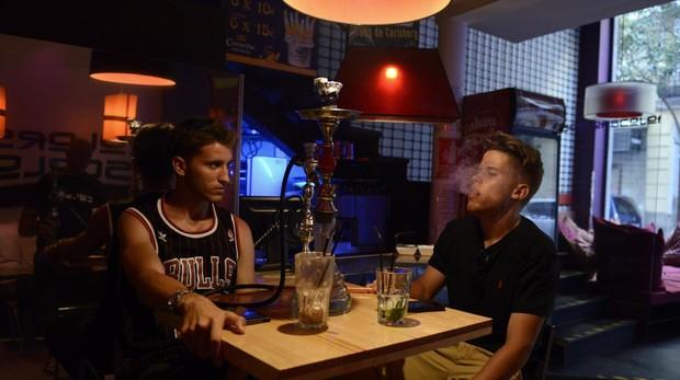 Dos jóvenes fuman cachimba en un establecimiento