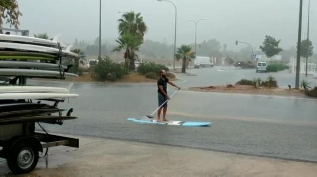 Un joven navega con una tabla de paddle surf en medio de una calle de Ibiza