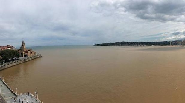 Las aguas marrones de la Playa de San Lorenzo, en Gijón
