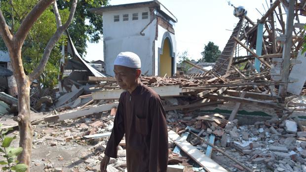 Un hombre pasa por delante de varios edificios derribados por un terremoto en Lombok