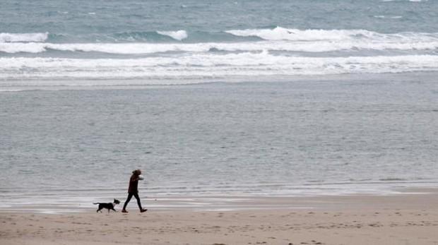 Un hombre y su perro pasean por la playa de Sabón en la localidad coruñesa de Arteixo
