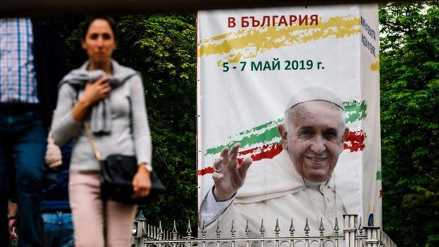 Una mujer camina junto a un cartel del Papa en Sofía, Bulgaria