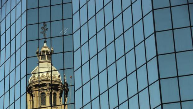 ista de una de la cúpulas de la catedral de Santiago reflejada en un edificio