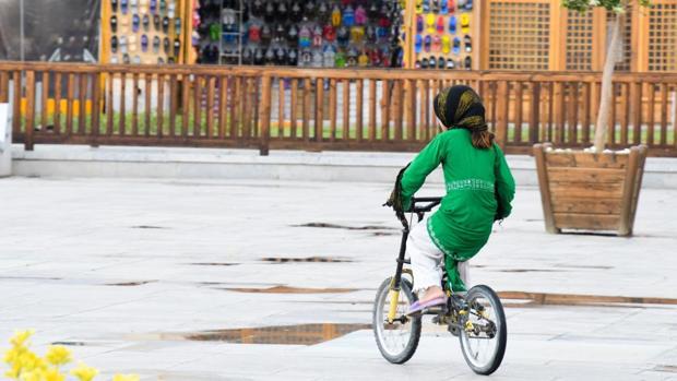 Niña en bicicleta con velo en Irán