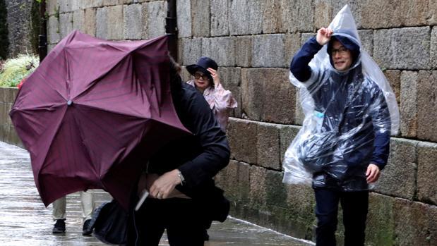 Turistas japoneses luchan por no perder sus paraguas en Santiago de Compostela