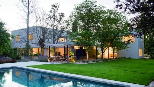 Exterior y jardín con piscina de Casa L en Pozuelo y salón de Proyecto Ch en la Moraleja, ambos trabajos de Ábaton-Blanca Alonso