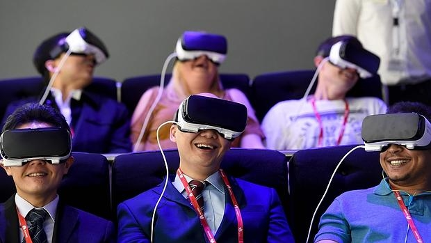 Varias personas prueban las gafas Gear VR de Samsung