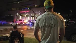 Un hombre luce una camiseta con un mensaje de apoyo a la policía mientras observa la entrada a emergencias del hospital Baylor