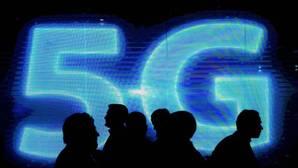 Varias personas pasan cerca de un cartel de 5G