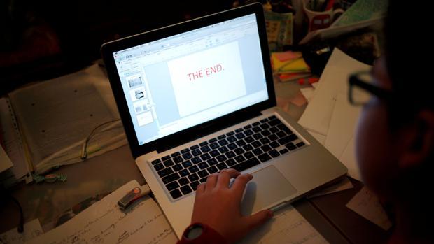 Un niño hace los deberes en el portátil