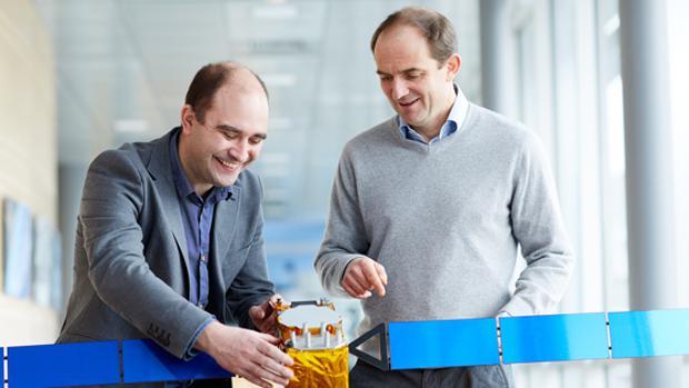 José Ángel Ávila Rodríguez (izq) y Laurent Lestarquit (der) cogiendo un modelo de satélite