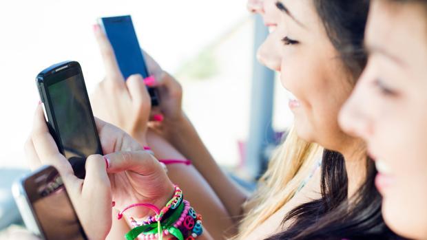 Varias jóvenes consultan sus teléfonos móviles
