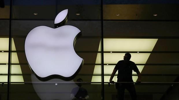 Un hombre cerca de un logotipo de Apple, durante la salida a venta del nuevo iPhone X