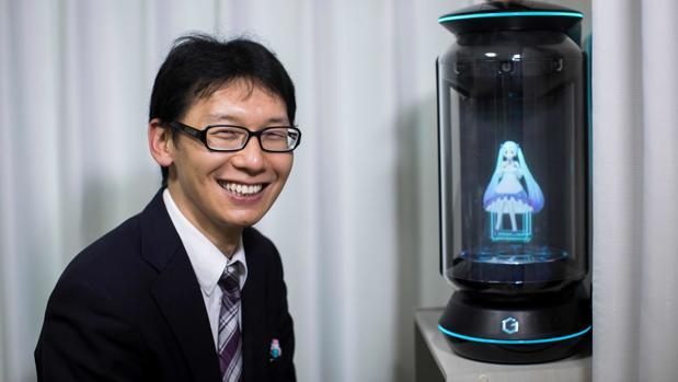 El joven posa con su esposa en forma de holograma