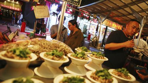 Varias personas compran comida en el antiguo mercado nocturno de Donghuamen, en Pekín