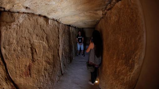 Una mujer toma una foto dentro de uno de los dólmenes de Antequera