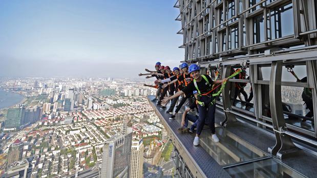 Un grupo de personas camina sobre una pasarela acristalada en el piso 88 de la Torre Jinmao en Shanghái (China)