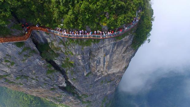 Turistas caminan por la nueva plataforma de cristal de Zhangjiajie, en la provincia de Hunan, China