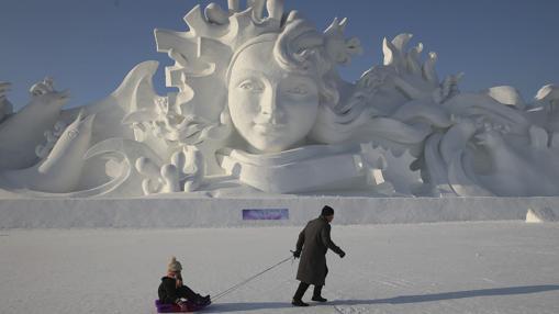 Un hombre y su hija juegan junto a una escultura de nieve de 31 metros de alto en la trigésimo tercera edición del Festival Internacional de Hielo y Nieve de Harbin (China)