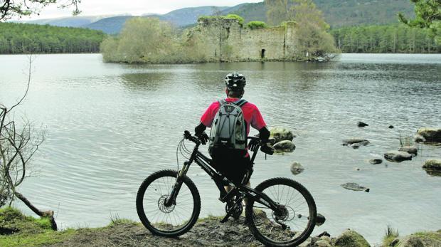 Un ciclista disfruta de la vista del Loch an Eilein, lago situado en Aviemore, en el corazón del Parque Nacional de Cairngorms (Escocia)