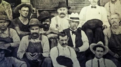 Fotografía tomada en 1900. Jack Daniel (hombre de barba y sombrero blanco del centro), sentado junto a un hombre afroamericano. Se cree que es George Green, hijo de Nearest Green