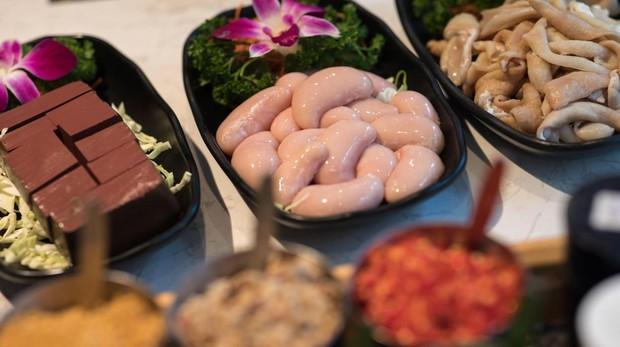 Una fotografía muestra platos de cubos de sangre de pato (izda), testículos de pollo (c) e intestinos de cerdo (dcha) en un restaurante de olla caliente en Hong Kong, China