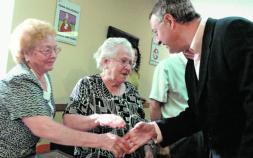 Jesús Caldera en una visita saludando a dos ancianas